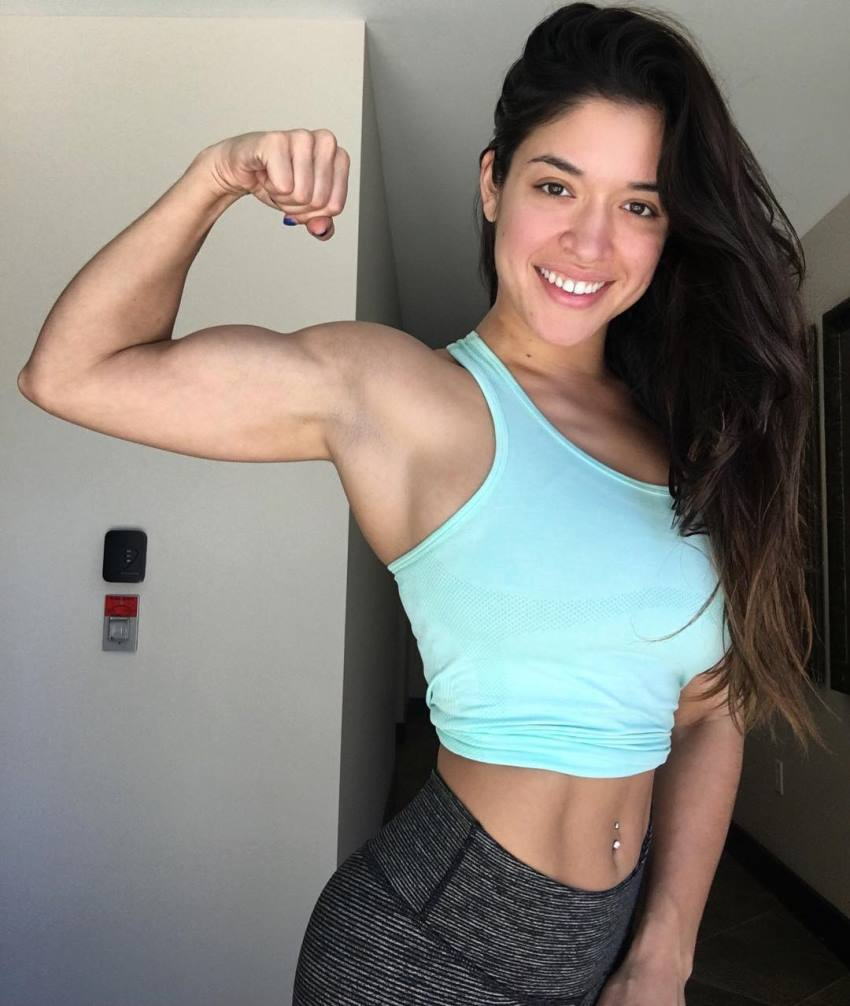 Noel Arevalo flexing her biceps and smiling