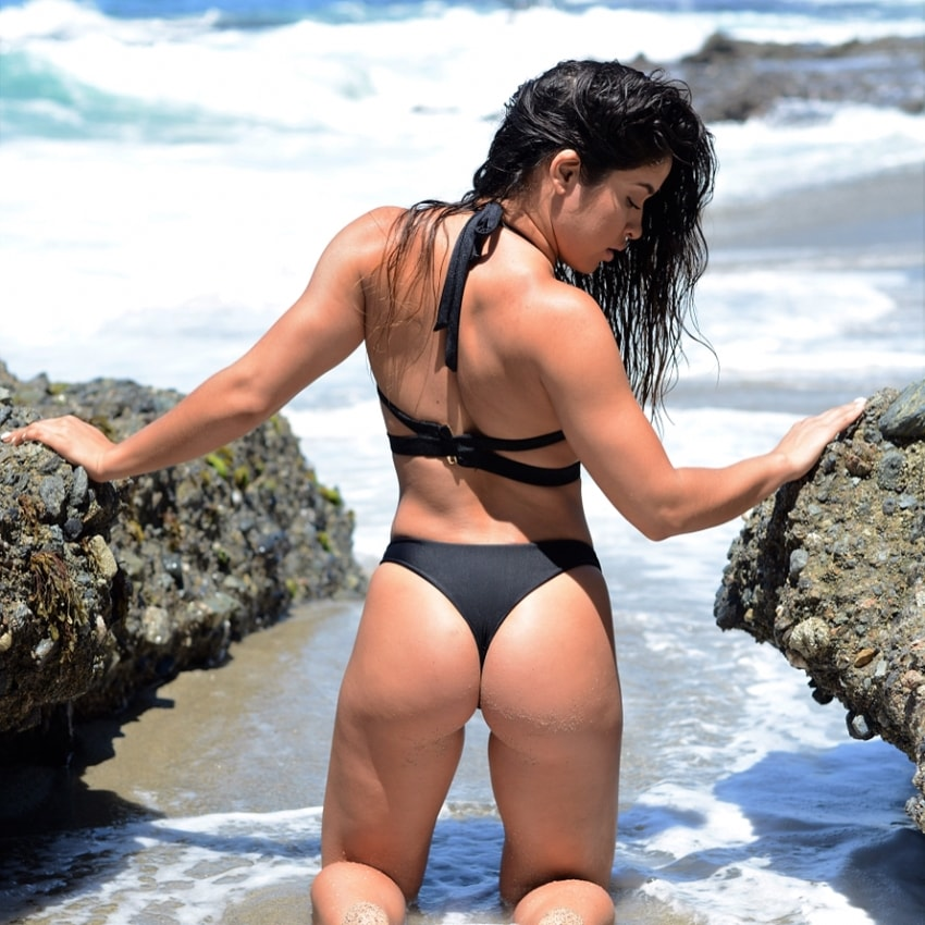 Noel Arevalo kneeling on a beach, with her hands on rocks, flexing her sensational glutes