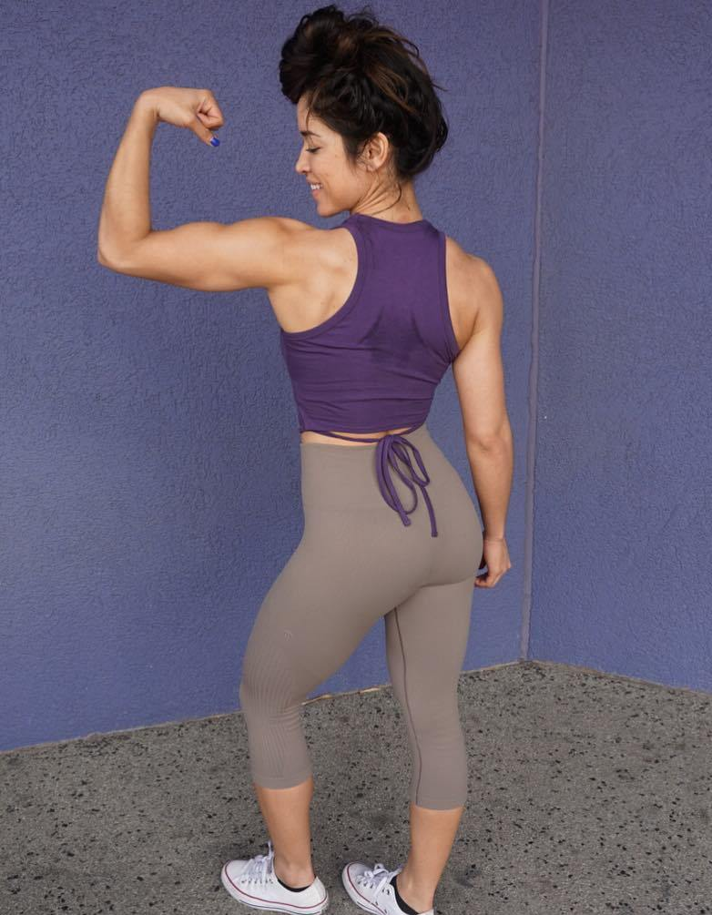 Noel Arevalo in grey yoga pants, flexing her biceps from the back, and smiling