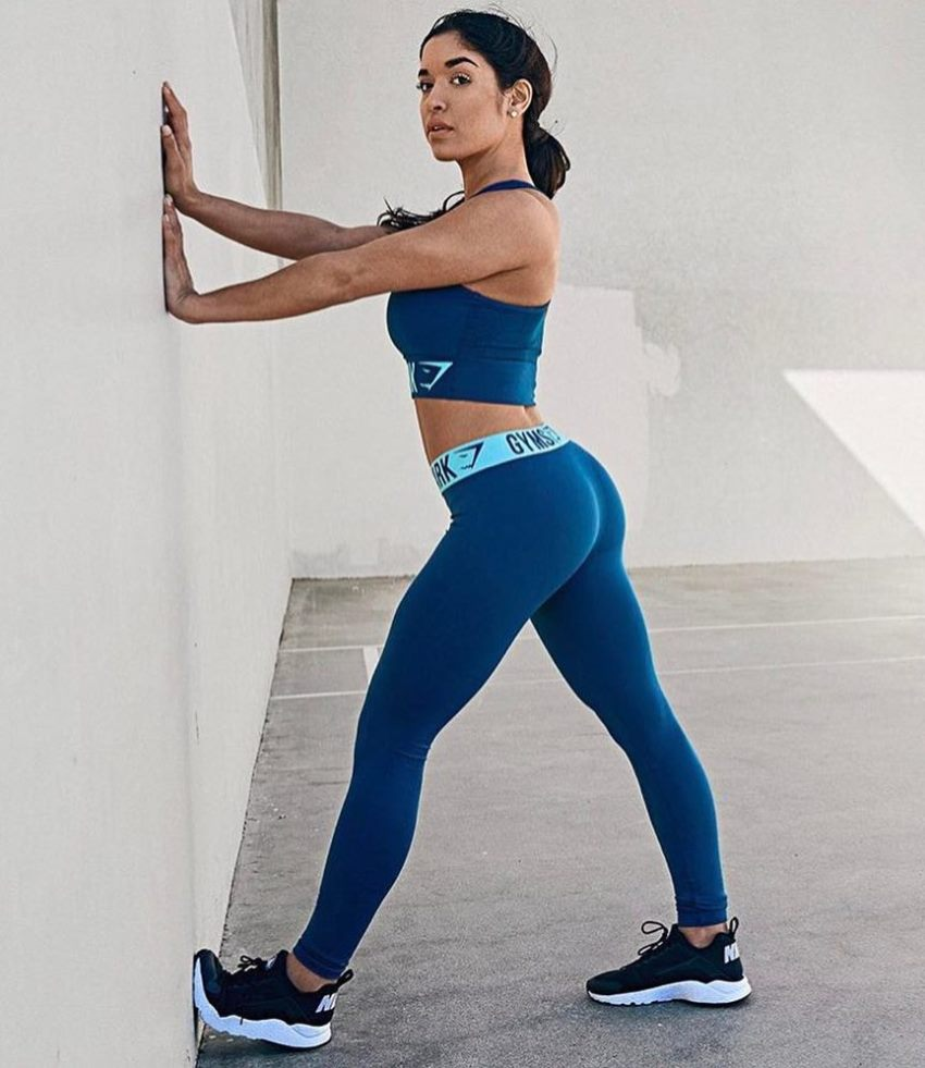 Noel Arevalo stretching against the wall in blue yoga pants, displaying her incredible leg and glute development