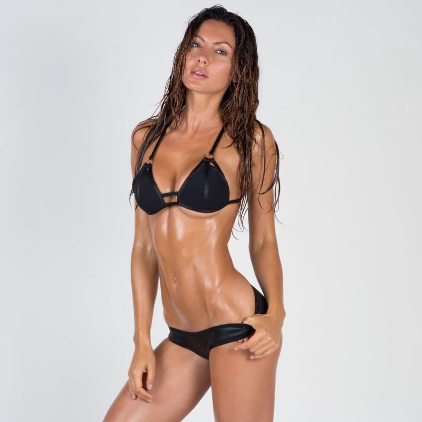 Oksana Rykova in a black bikini suit and wet hair, showing her lean body