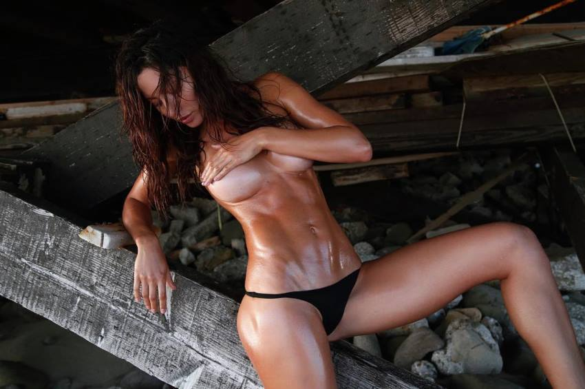 Oksana Rykova covering her breats as she unveils her oiled up, awesome abs and legs
