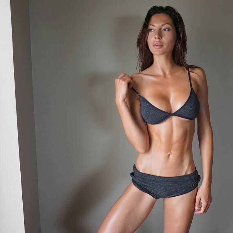 Oksana Rykova with a cast shadow behind her, looking somehwere in the distance, as she flexes her abs