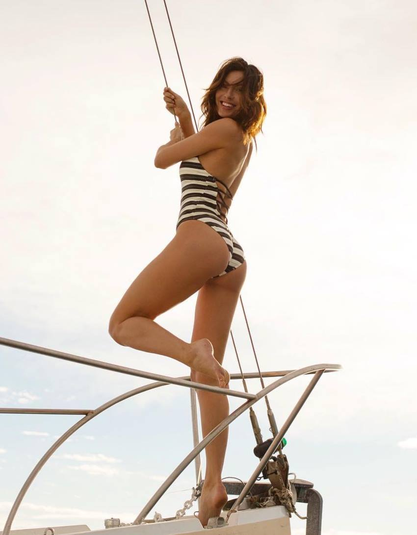 Oksana Rykova on a boat, showing her glutes and legs, while smiling at the camera