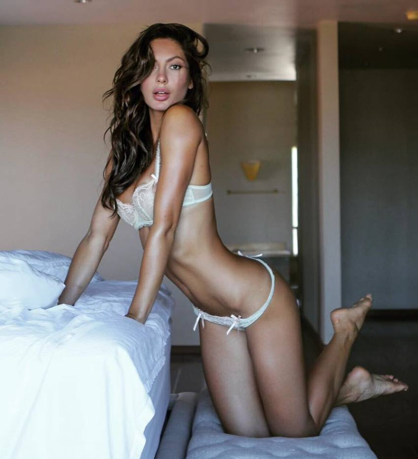 Oksana Rykova in a bedroom in a lingerie, as she looks into the camera and displays her lean figure