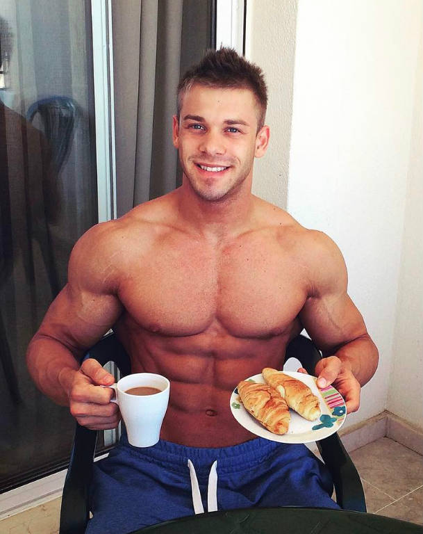 Ondrej Kmostak sitting down, eating a healthy meal and showing his large chest, abs and arms