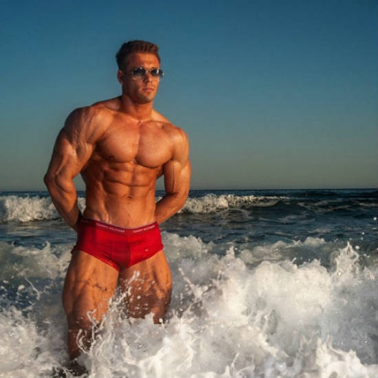 Ondrej Kmostak standing in the sea, showing his ripepd abs, large chest and arms