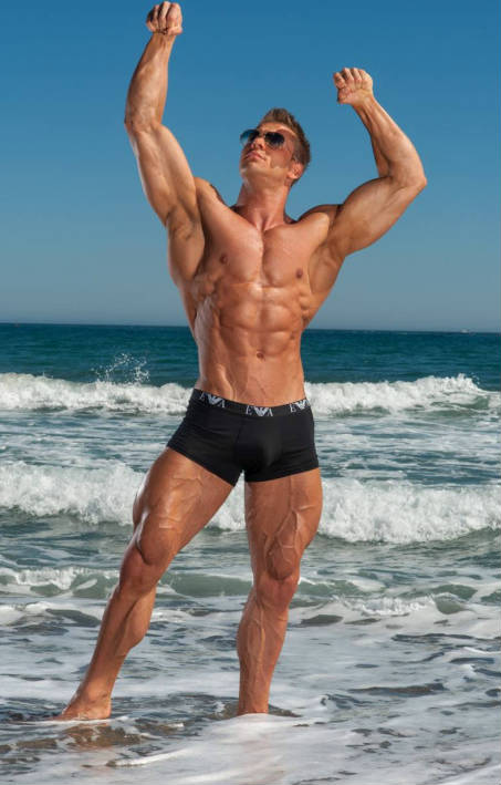 Ondrej Kmostak standing on the beach, showing his large arms, ripped abs and toned delts