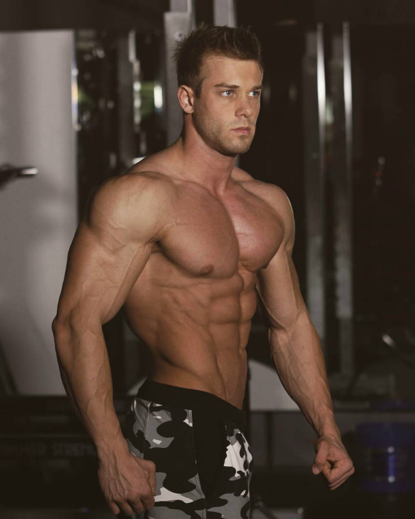 Ondrej Kmostak showing his ripped abs and large chest and delts