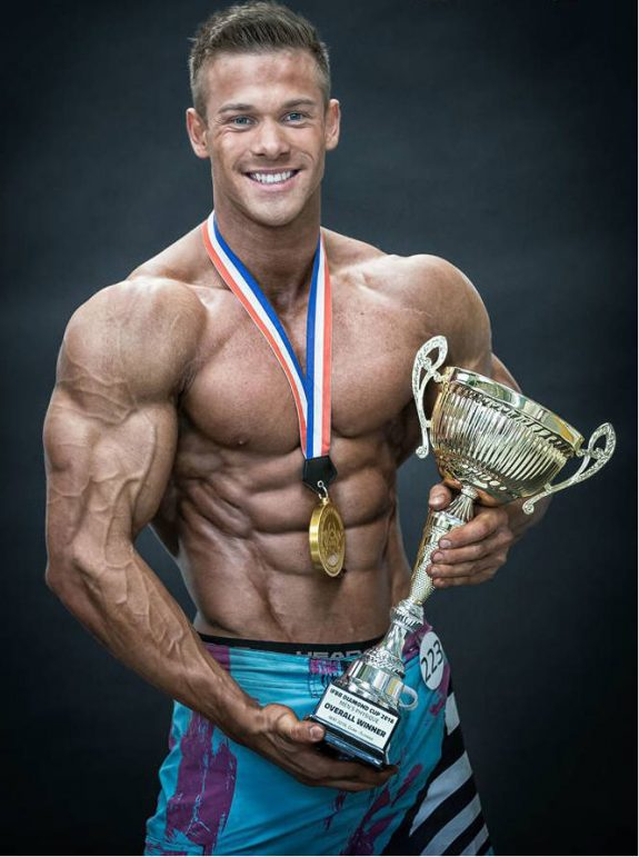 Ondrej Kmostak holding the winners trophy at a competition, displaying his ripped abs and large arms