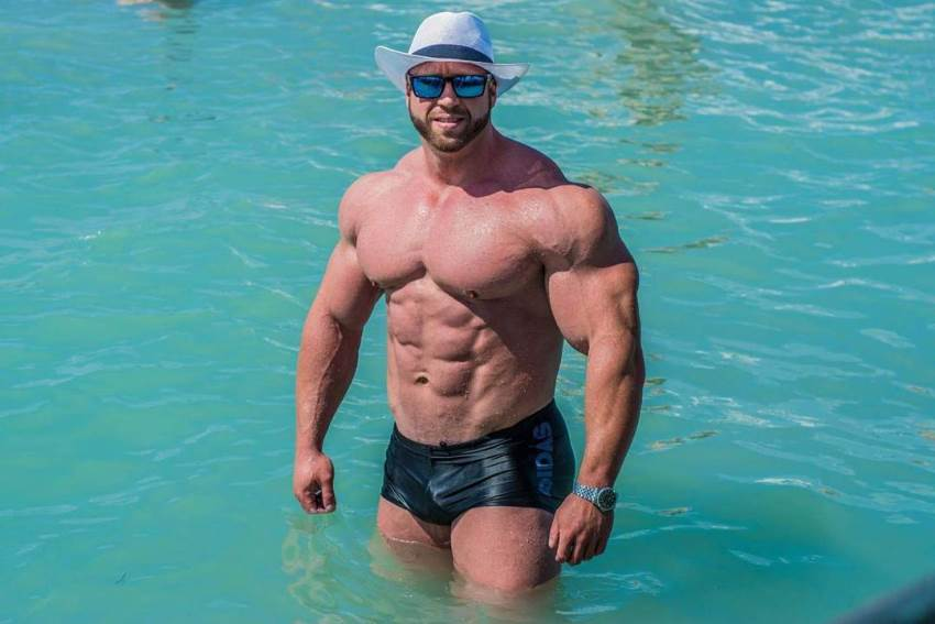 Petar Klancir standing in a pool with a white hat and blue shades on, showing off his massive and lean body