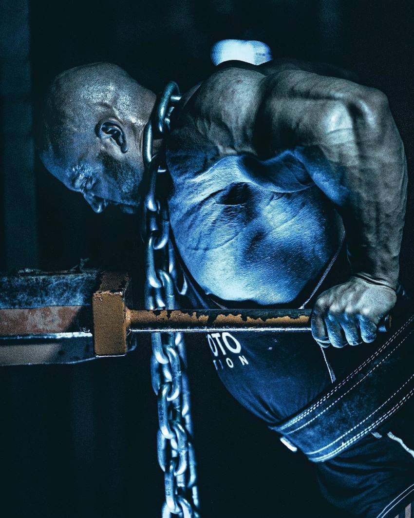 Petar Klancir doing dips with chains around his neck, his arms looking enormous and defined
