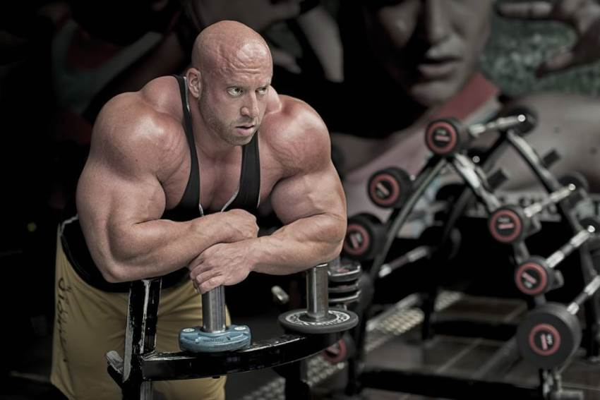 Petar Klancir leaning against a gym machine, looking at the distance, with his arms and shoulders looking massive and round