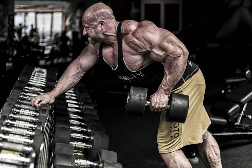 Petar Klancir leaning against dumbbell rack, doing single-arm bent over rows