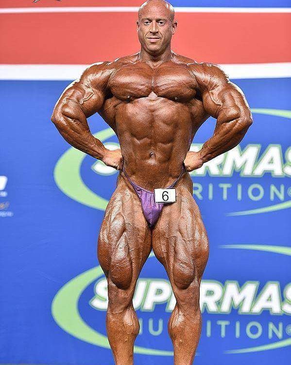 Petar Klancir on the stage, in a front lat spread pose, showing his extremely ripped physique to the audience