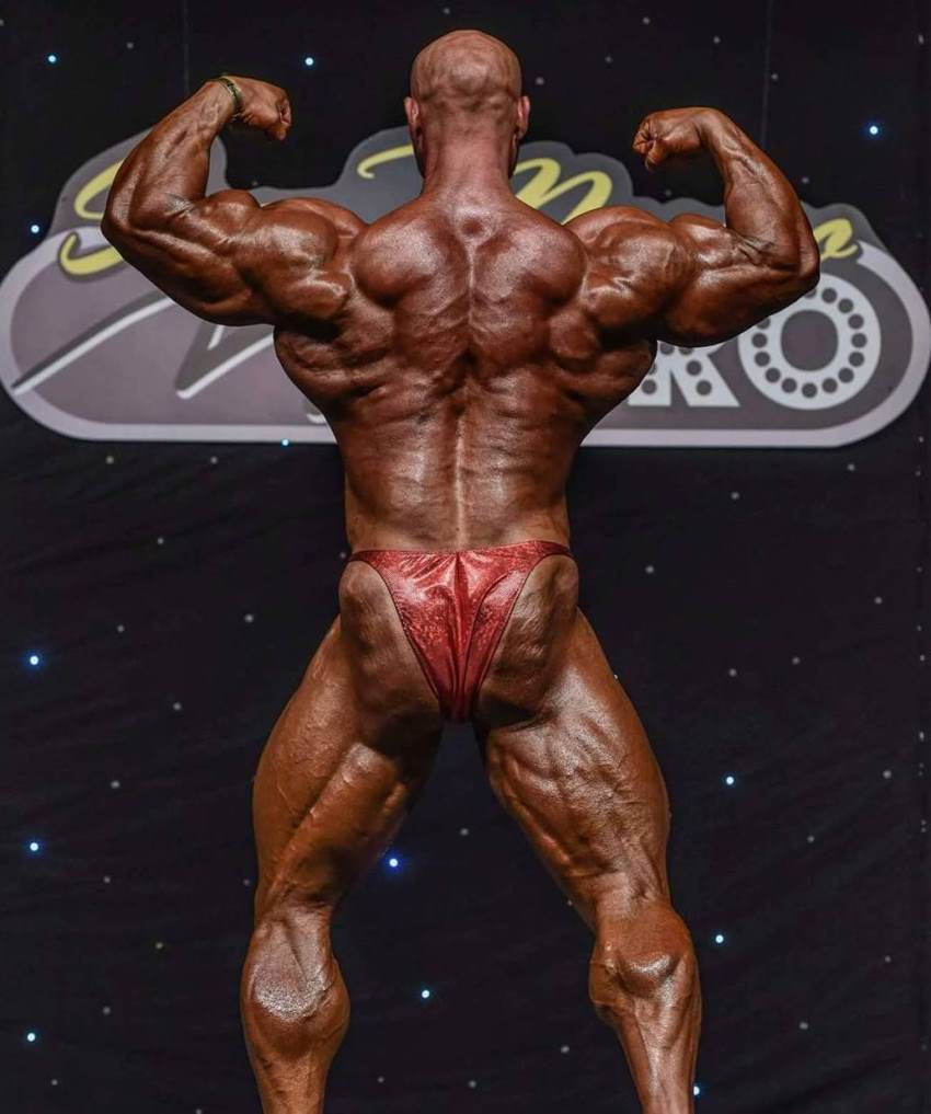 Petar Klancir on a bodybuilding stage in red trunks, holding an impressive back double biceps pose