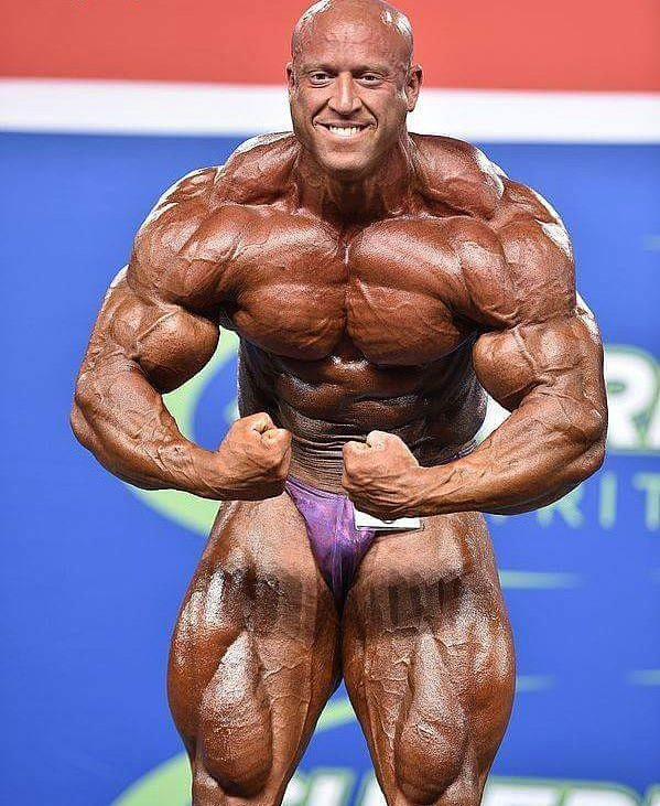 Petar Klancir on the stage, showing his most muscular pose to the auditorium