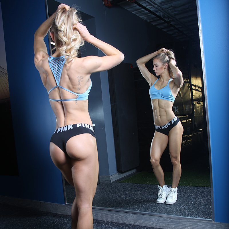 Rachel Scheer standing in front of a mirror, having both of her hands in her hair, as she shows her incredible legs, glutes, back, and abs