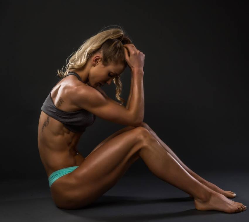 Rachel Scheer sitting on a floor as she contemplates about something, showing her lean physique from the side
