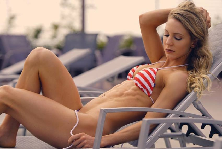Rachel Scheer lying on a beach chair in a red and white bikini, having one of her hands in her hair, and showing off her lean figure