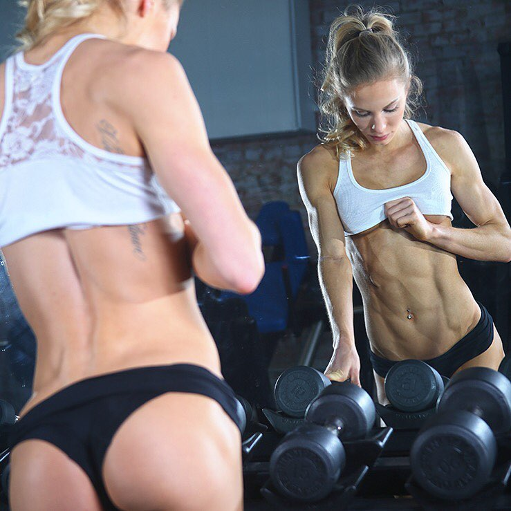Rachel Scheer checking her abs in front of a gym mirror with weights