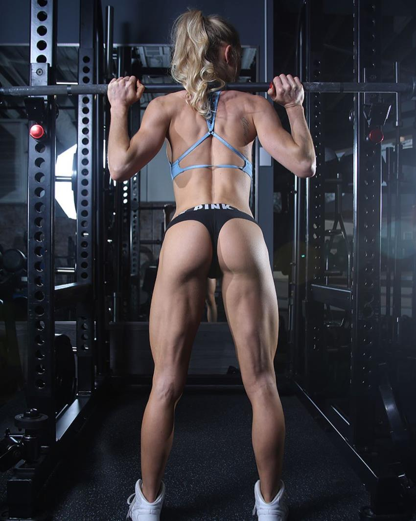 Back shot of Rachel Scheer doing squats in a bikini, revealing her aesthetic body