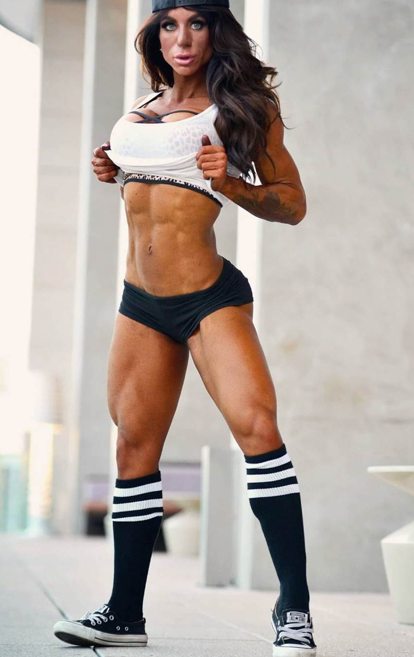 Rachelle Carter in long black socks with white stripes and revealing sportswear, flexing her abs and legs