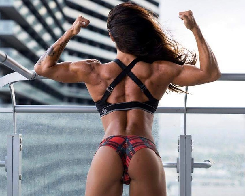 Rachelle Carter doing a back double biceps pose, displaying her incredible arm, back, and leg development