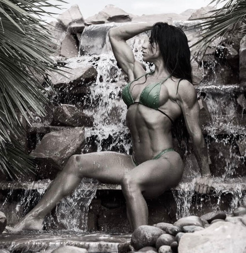 Rachelle Carter sitting on a water stream on rocks, as she shows her incredibly lean physique in a bikini
