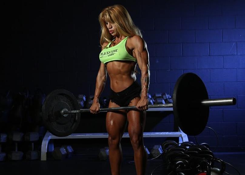 Rachelle Carter doing a lift with a barbell, while flexing her awesome physique