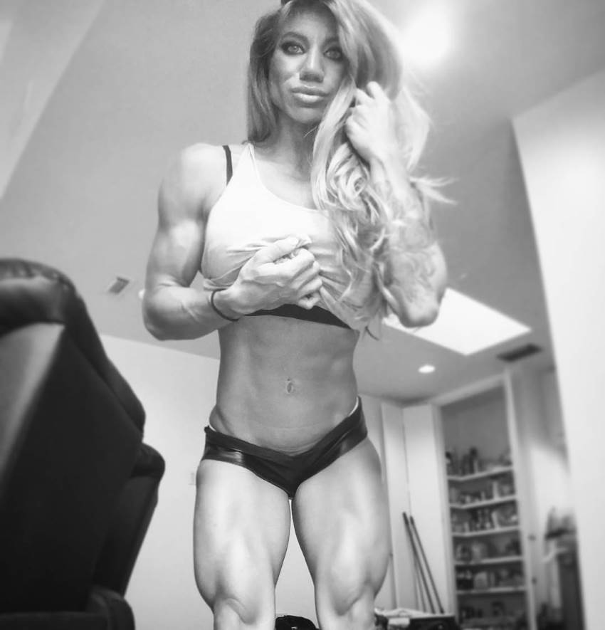Rachelle Carter flexing her arms, abs, and legs for the camera, with one of her hands in her hair