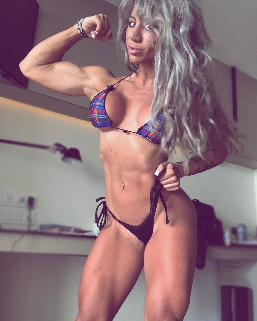 Rachelle Carter doing a flex double biceps pose in a room, showing her ripped arms and legs
