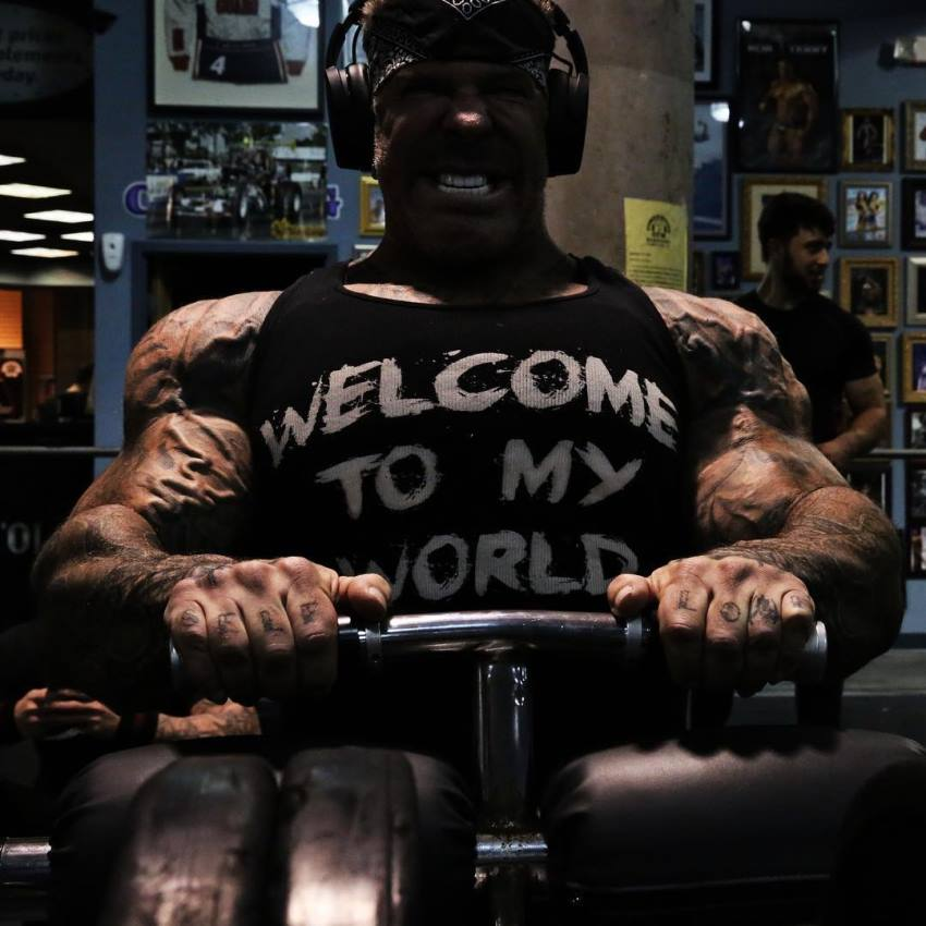 Rich Piana doing seated calf raises in a black tank top and headphones over his head, having a pained face expression as he does the exercise