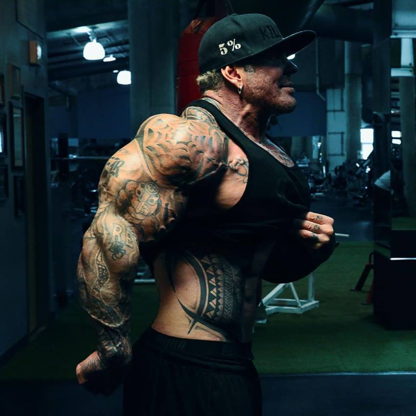 Rich Piana showing his monstrous arms from the side, as well as doing vacuum while lifting his black tank top
