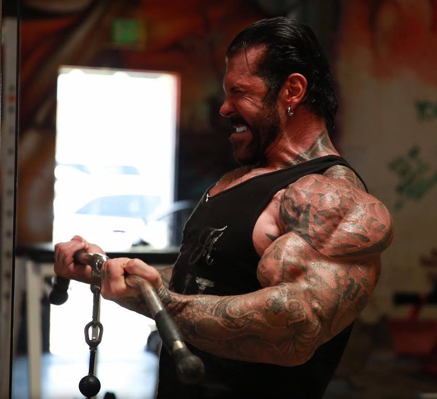Side shot of Rich Piana doing cable biceps curls with his incredibly big arms