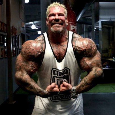 Rich Piana in a white tank top with black outlines, flexing his arms for the camera, as he stands under the perfect downlighting which accentuates his physique