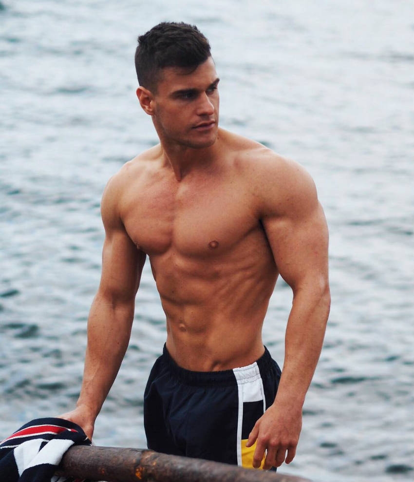 Rob Lipsett standing next to the ocean, showing his ripped abs, obliques and large delts