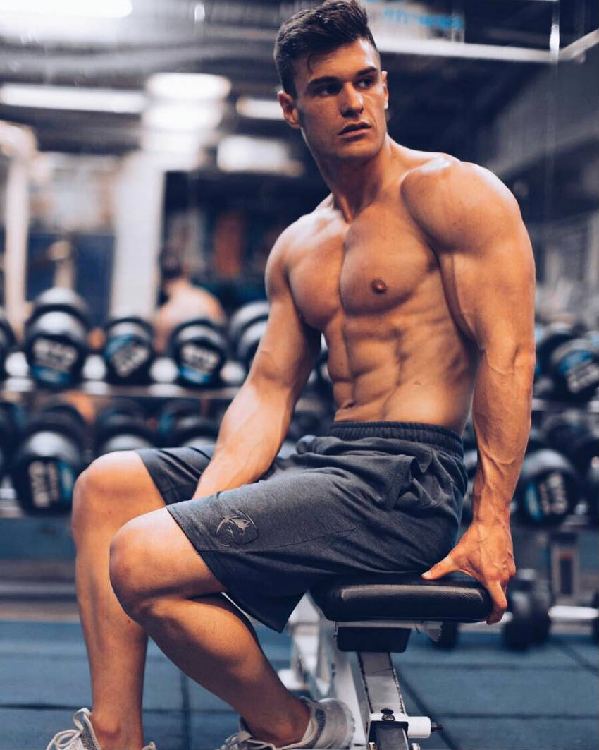 Rob Lipsett sitting on a gym bench, showing his ripped abs, large delts and vascular foreamrs