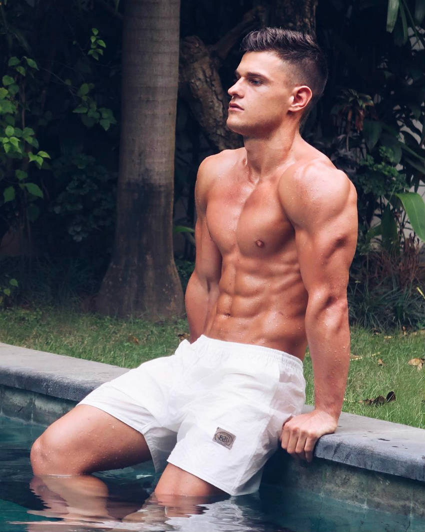 Rob Lipsett sitting by a pool, showing his large triceps, ripped abs and sculpted chest
