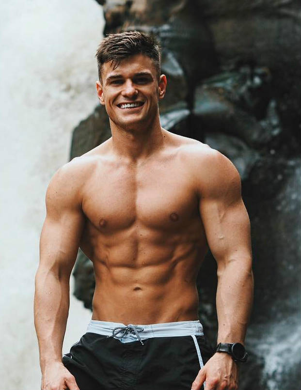 Rob Lipsett standing in front of a waterfall, showing off his ripped abs, large chest and toned delts