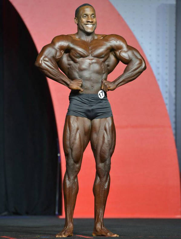 Robert Timms posing at a classic physique competition, showing his large chest, quads and arms