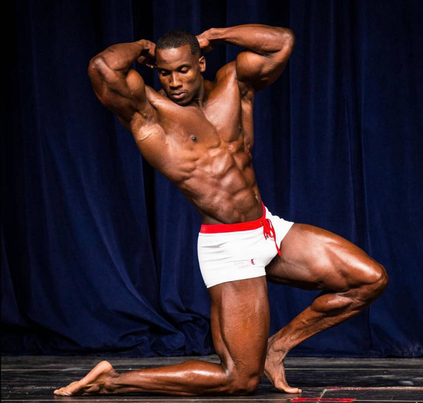 Robert Timms kneeling down at a competition, showing his large quads, obliques, abs and arms