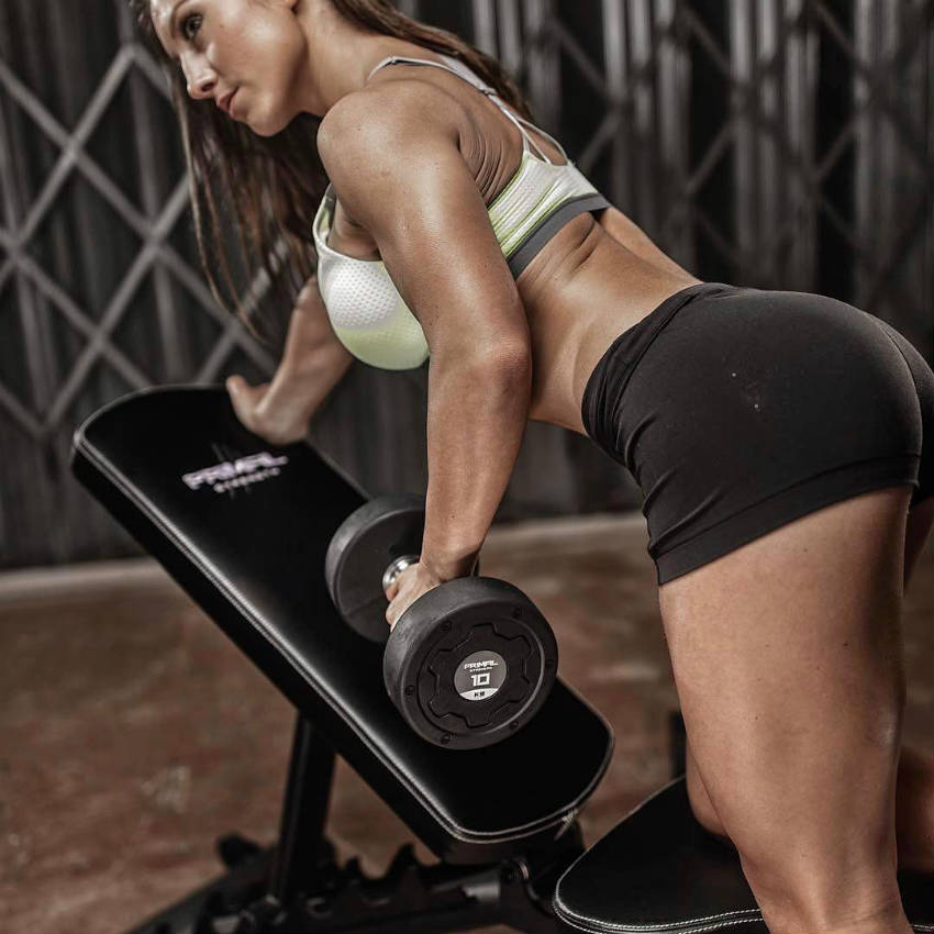 Sandra Radav completing a bent over dumbbell row, showing her pumped tricep and deltoid