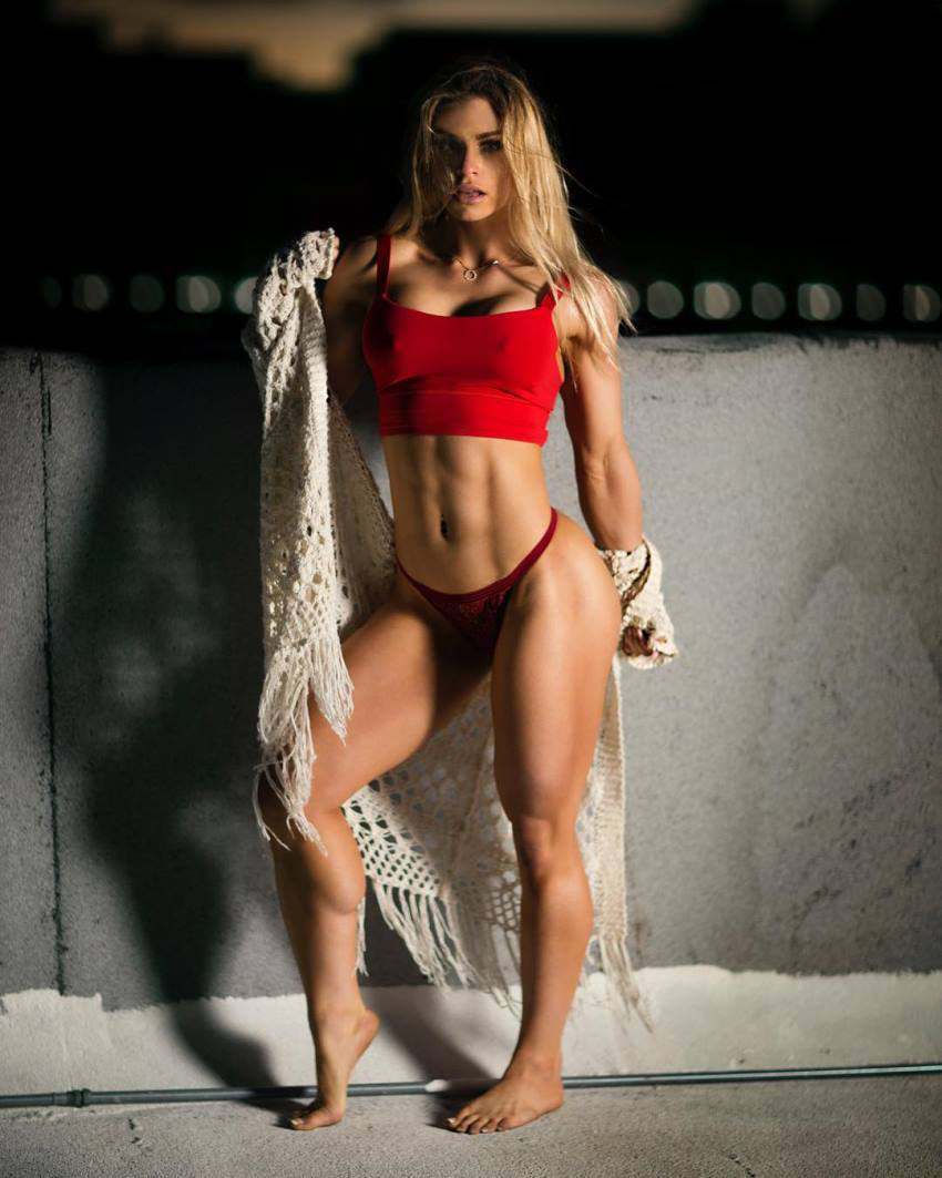 Syleena Adams posing for a photo in a red bikini and sportsbra, flexing her awesome abs and legs
