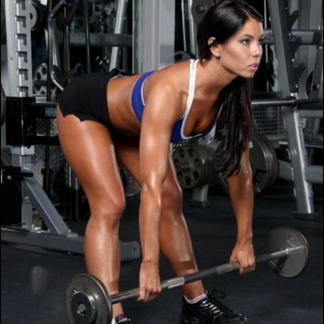 Tara LaValley completing a bent over barbell row, showing her delts and legs