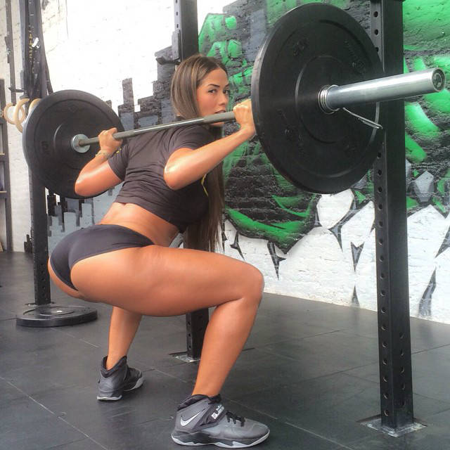 Tatiana Girardi completing a squat, showing her toned glutes and quads