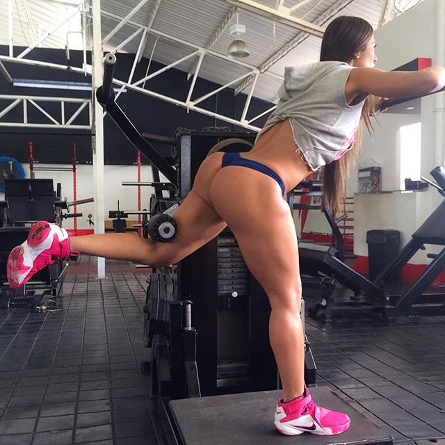 Tatiana Girardi completing a standing leg raise, showing her toned quads am glutes