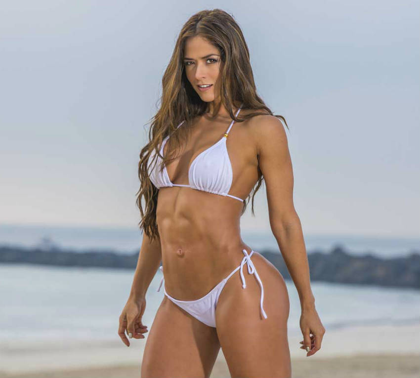 Tatiana Girardi standing on the beach showing off her toned abs, large quads and glutes and toned arms