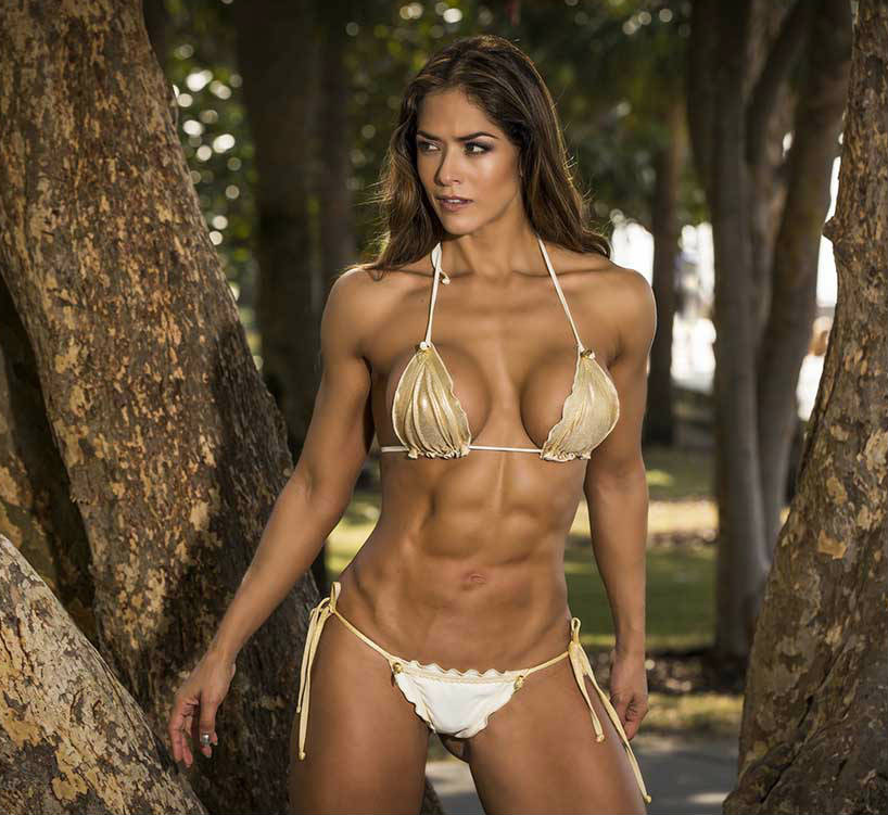 Tatiana Girardi standing in the woods, showing off her toned abs and chest in a bikini