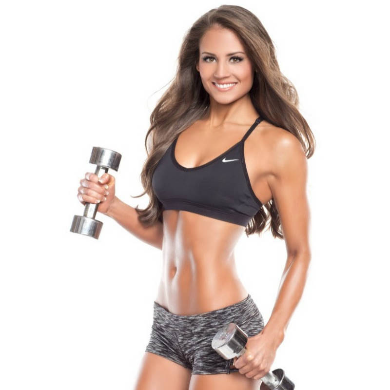 Taylor Chamberlain holding two small dumbbells, showing her arm and ab tone